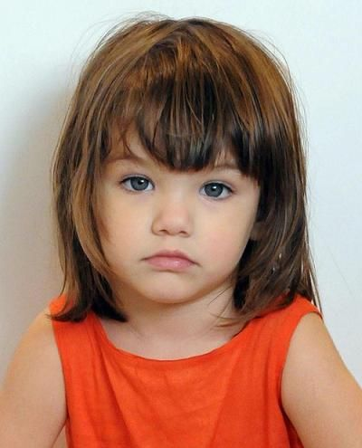 """Yes, this little girl is adorable.  But its her bangs that make the statement.  Short 'do with blunt bangs, of course messy because you just got in from """"'sploring the neighborhood""""."""