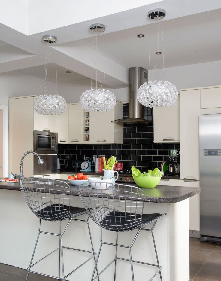 The chandelier style pendants above the island in this kitchen add a real touch of glamour. The light will reflect all around the room and create a brilliant feel. Kitchens are often seen as a practical area, but with a bit of imagination it's easy to style them beautifully.