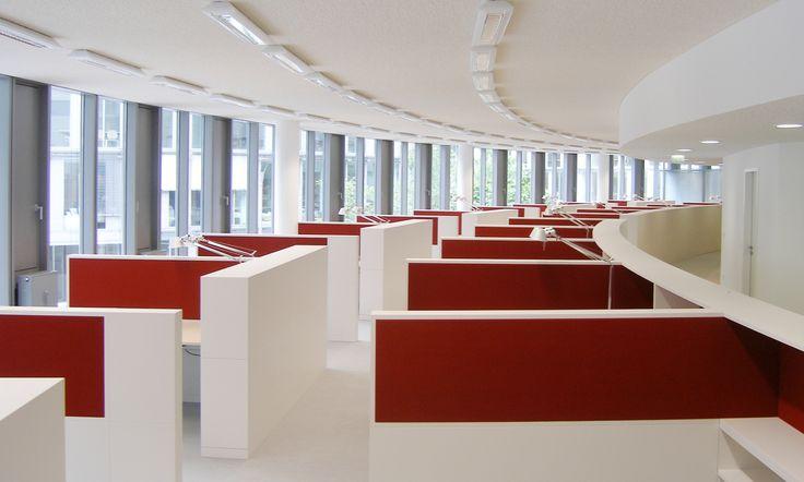 Dieses Großraumbüro besticht durch gerundete Elemente in lackierter Strukturlack Ausführung mit angedockten Einzelplätzen. Das besondere Design wird durch die stoffbespannten Dämmelemente abgerundet.