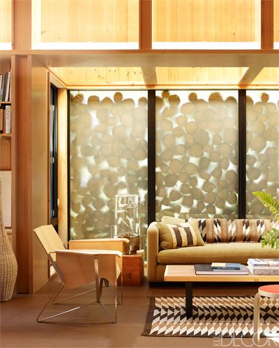 A wall of sandblasted glass backed by stacked cedar logs in the living area of this lakeside home.