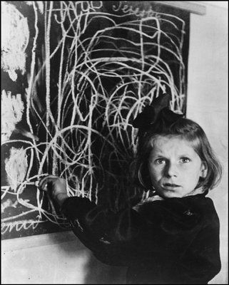 """Poland.  A child survivor of a concentration camp draws a picture of """"home"""" on the blackboard"""
