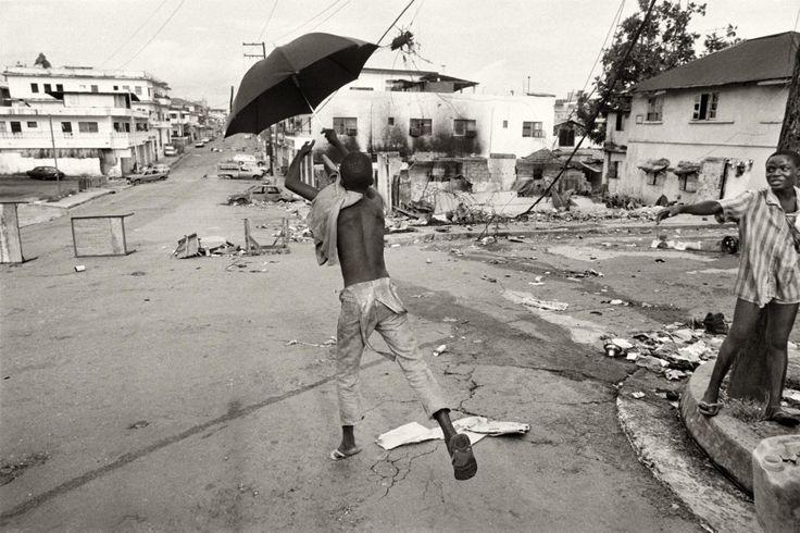 Un niño salta con un paraguas abierto en una ciudad destrozada por los combates. Monrovia (Liberia), mayo de 1996. Fotografía de Gervasio Sánchez