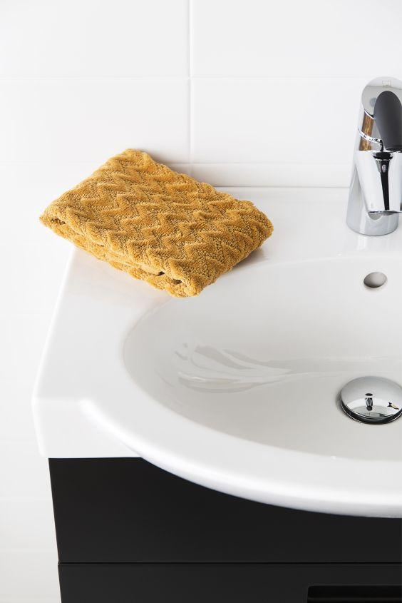 Piristä mustavalkoista kylpyhuonetta värikkäillä tekstiileillä.