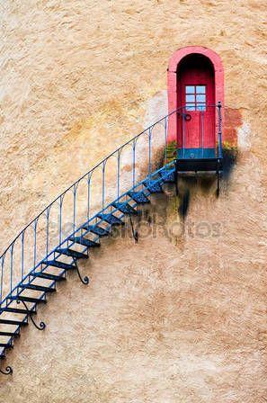 Украшенные лестницы, ведущей к двери в терракотовые стены