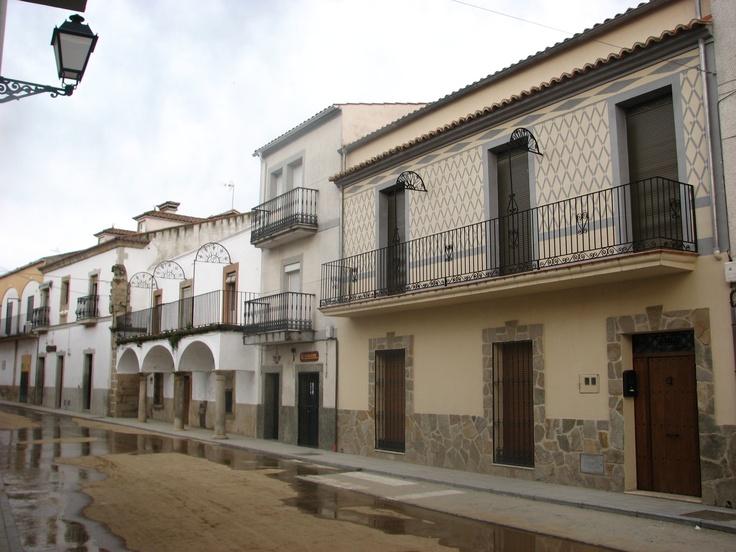 Hermosa calle de Navas del Madroño, calle Francisco Pizarro, con la casa de los portales al fondo.