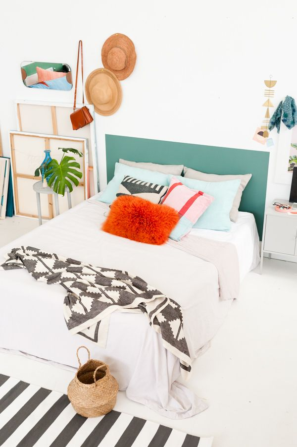 An artsy loft bedroom with a diy painted headboard