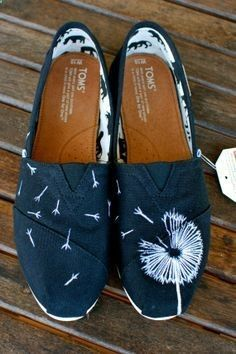 This pair of custom, hand painted black canvas classic TOMS shoes features my whimsical design of a white dandelion blowing in the wind with the seeds of the dandelion blowing from one shoe to the oth