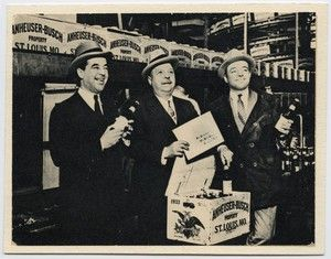 Adolphus Busch III, August Busch Sr., August Busch Jr. pose with first case of post Prohibition repeal beer that was sent to President Franklin Delano Roosevelt after the end of Prohibition.. August Busch Sr. holds envelope addressed to the White House. (1933)