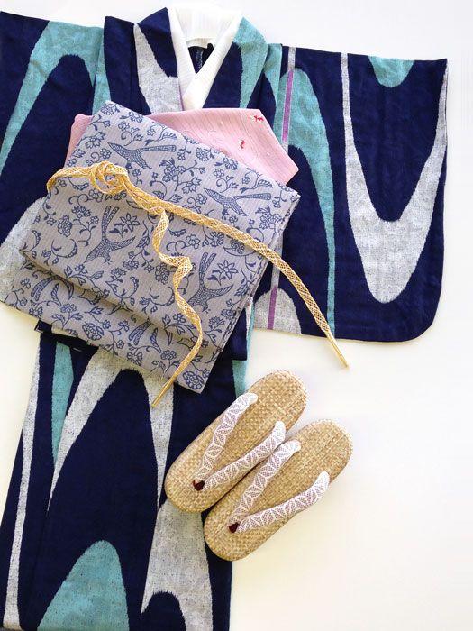 《今日の着物コーディネート》初夏を感じさせる鮮やかブルーの単衣の着物です。綿レースの生地に流線型の模様が入りとっても涼しげな印象です。同じく綿の名古屋帯には唐草模様が、絽の帯揚げには金魚の刺しゅうが施され、季節を先取り出来るコーディネートです。レースの帯締めにはイエローで挿し色に。夏の外出にお勧めなのがブランド「ketoy」の白木天はり草履。すっきりとした初夏の着物おしゃれをお楽しみください。