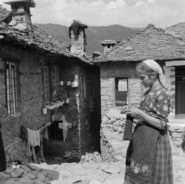Greece, woman knitting outside homes in Métsovon