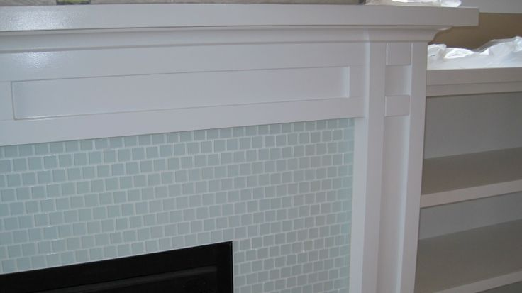 white fireplace with tile, bookshelf on each side