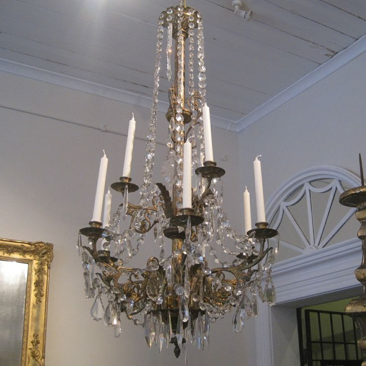 French Bronze And Crystal Chandelier have cascading crystals and crystal prisms throughout. Candlelit and later electrified. An original candle lit light with nine candleholders and now electric light emanating from the base. Lovely patinated bronze with decoration.
