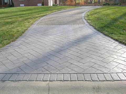 This stamped concrete driveway combination is poured in a cobble gray color with a charcoal release. It entails gray exposed aggregate centers, ...