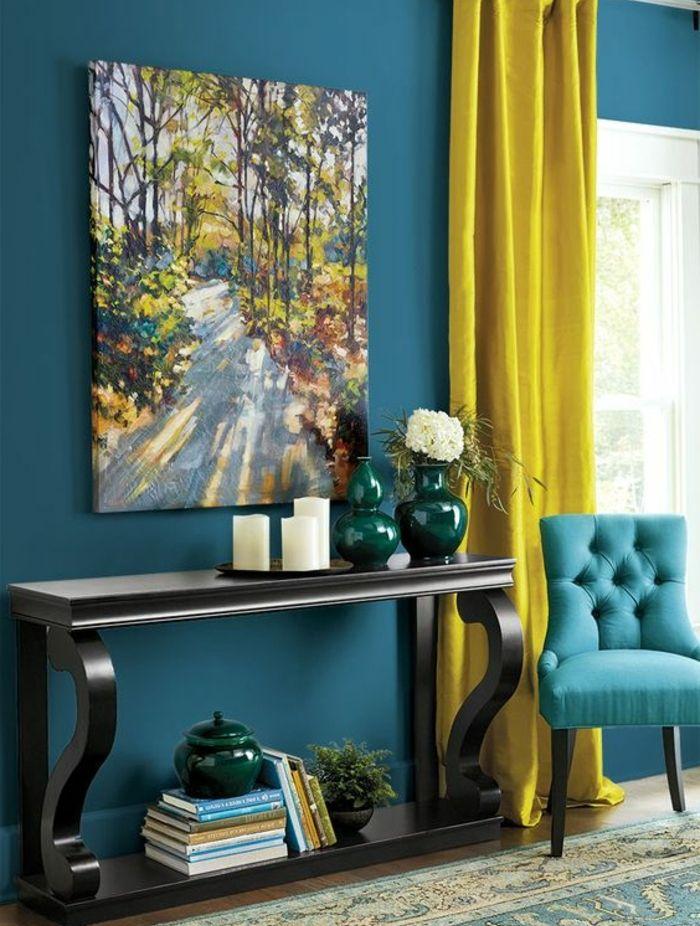 deco bleu canard et jaune, table de service en bois, mur et canapé couleur bleue, tableau peinture paysage foret, bougies vases, livres, tapis oriental, rideau jaune