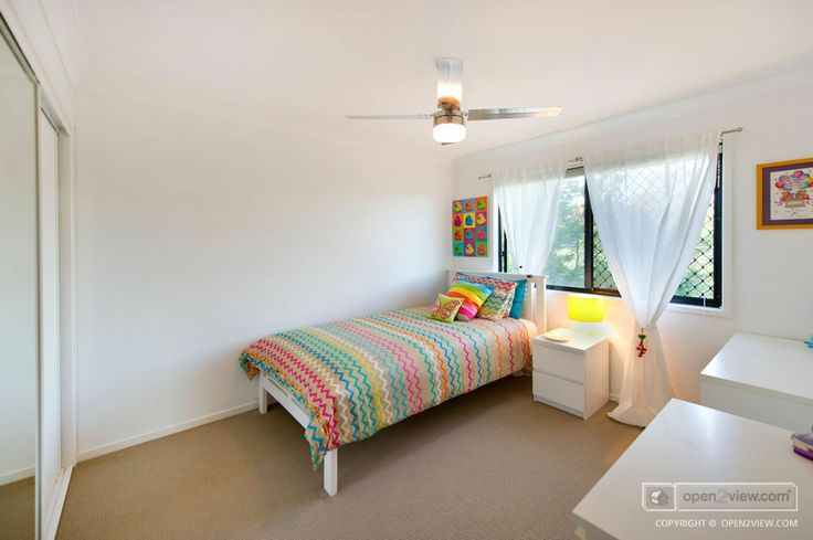 Kid's room kept simple. Neutral tones with colour accents in the artwork and bed coverings.