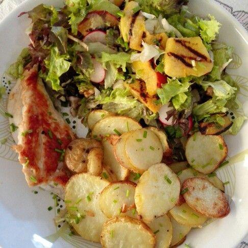 Gebakken aardappelen, salade met gegrilde perzik en kippendijfilet.
