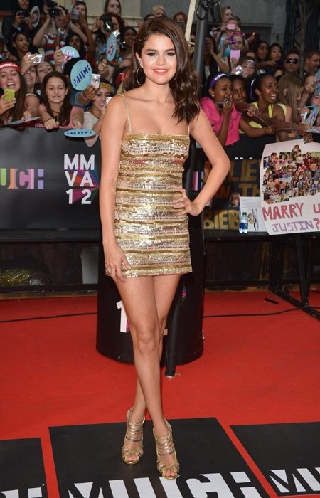 Teen queen Selena Gomez shows up in a gold mini-dress which shows off her killer legs, but where is her boyfriend, Justin Bieber? The dress certainly leaves not much to the imagination but what a way to make an entrance! (Photo by George Pimentel/WireImage
