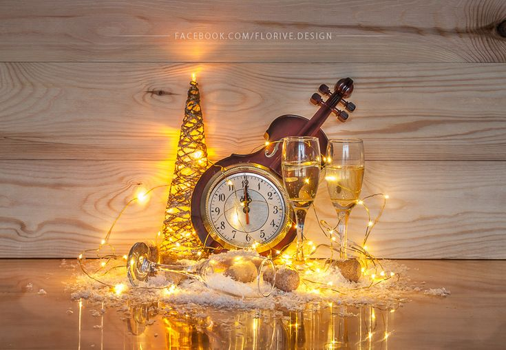 Shiny New Year's decoration with a decorative clock, golden christmas tree and glasses of sparkling champagne on a wooden background