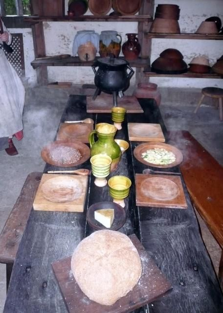Winkhurst Tudor Kitchen: Low table set up, wooden trencher plates, wooden spoons, mugs for small beer. Also bread and local cheese are on the table and cauldron of pottage. On the left is frumenty and on the right re-fried beans.