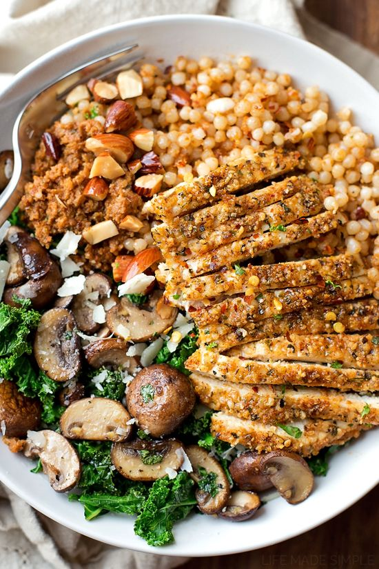 A quick pesto-like sauce brings this flavorful and filling parmesan chicken with sun-dried tomato cous cous and garlic veggie bowl together.