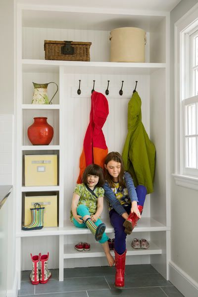 Situated near the back door and away from the cooking zone, this mudroom built-in holds cubbies and a boot bench for kids. | Photo: Eric Roth
