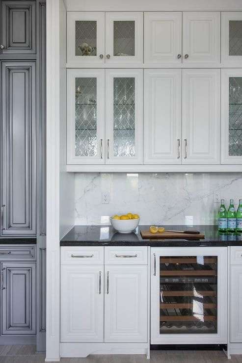 Chic kitchen bar boasts white cabinets fitted with leaded glass cabinet doors paired with black granite counters and a gray and white marble slab backsplash.