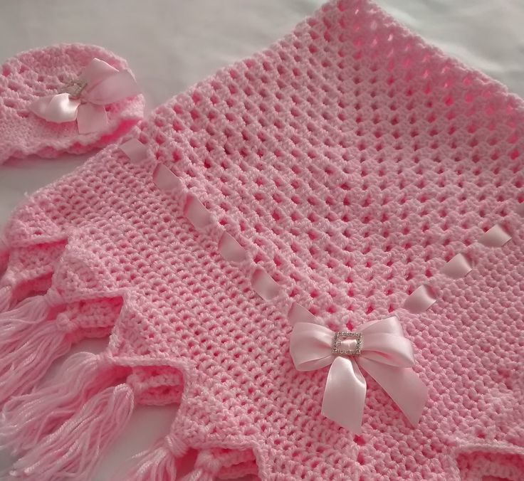 A crochet shawl & a matching beanie hat. They have a small diamante buckle on the ribbon bows