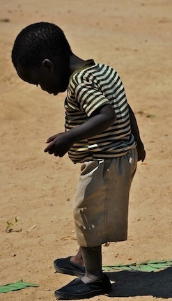 A young boy in Malawi checked out his new TOMS shoes just after he received them from TOMS Giving Partner Goods for Good.