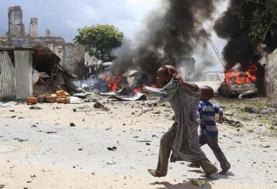 A Somali girl and her brother run to safety near the scene of a blast in Mogadishu, April 14, 2013