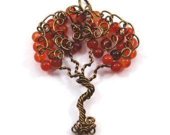 Un hermoso colgante que parece un árbol de naranja California. Granos de la cáscara de naranja y verde con el alambre color cobre antiguo entrelazan para crear un hermoso árbol. Se trata de una representación de la botonera, recibirá. Cada pieza creada es único. Usted también recibirá una cadena coincidente de 22 pulgadas.  En la parte delantera de la botonera puede ver remolinos creados a partir de alambre. En la parte posterior los granos de la viruta de peridot son más prominentes. Puede…