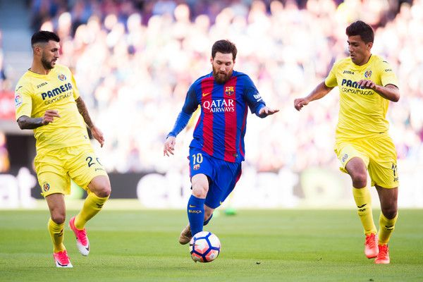 Lionel Messi (C) of FC Barcelona competes for the ball with Roberto Soriano (L) and Rodrigo Hernandez (R) of Villarreal CF during the La Liga match between FC Barcelona and Villarreal CF at Camp Nou stadium on May 6, 2017 in Barcelona, Catalonia.