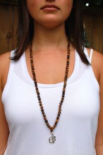 Tiger Eye is a grounding gemstone rooted in confidence and power. It synthesizes the energies of the Sun and the Earth. It brings a boost to the solar plexus chakra and helps to discipline sexual and emotional life. Tiger Eye brings optimism to the user and balances the yin-yang energy.  This mala is complimented by 92.5% silver OM pendant. It has been cleansed in the Ganga in Rishikesh, India, the holiest river in the world.   *The healing properties inherent in each mala are the…