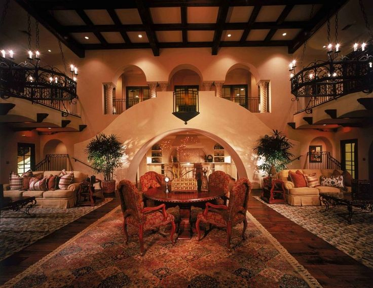 Mediterranean Living Room With Hardwood Floors, Wall Sconce, High Ceiling,  Carpet