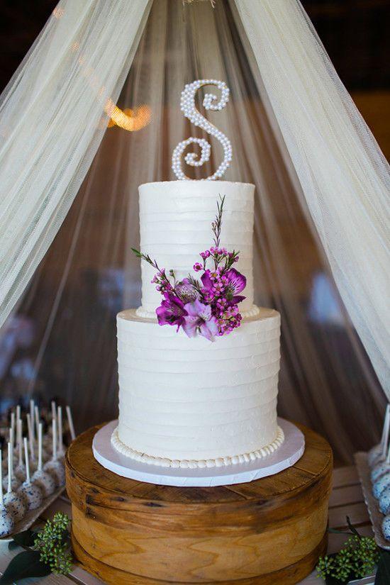 紫色の花と初期トッパーと古典的な白いウェディングケーキ