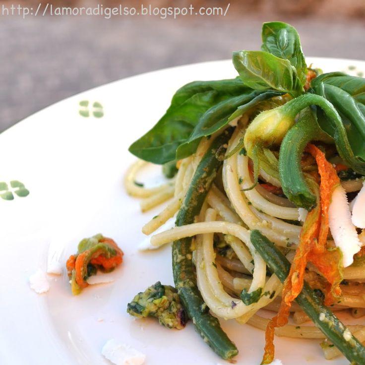 Gli spaghetti al pesto di pistacchi e pinoli con i fiori di zucca, i fagiolini e la ricotta salata