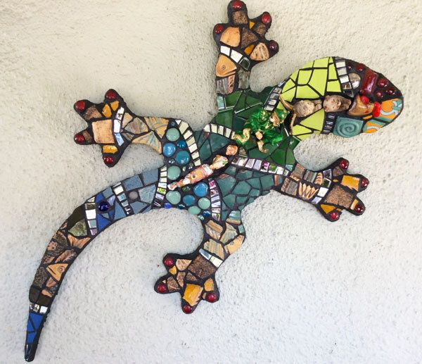 Lizard. Cement on Wediboard substrate. Mosaicked in pique assiette style using figurines, recycled glass, found objects, china, tiles, mirror. 3 feet long.