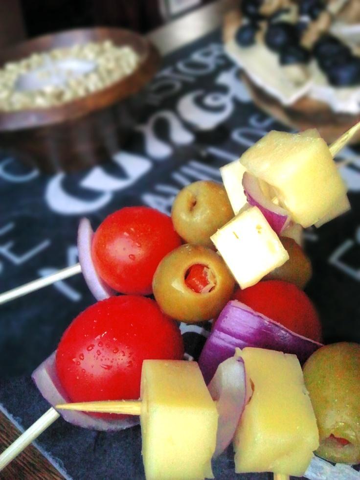 Brochetas de queso de cabra, tomates cherry, aceitunas rellenas con pimentón y cebolla morada.  www.box.echef.cl