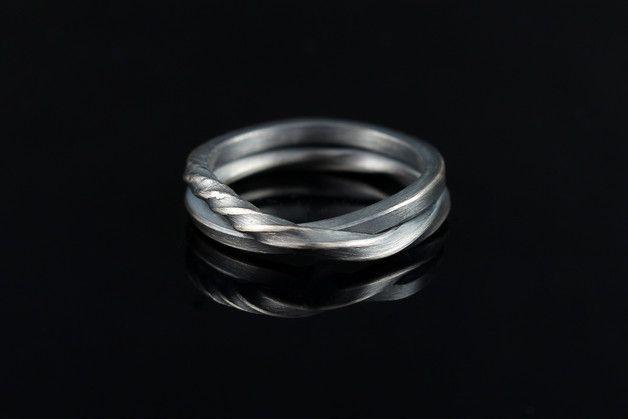 **Das Schmuckstück**  Gummiband oder Silber? Dieser spannend gekordelte geschwärzter Silberring hat die Optik eines gedrehten Gummibandes. Ob als Schmuckring, Ehering oder Freundschaftsring, dieser...