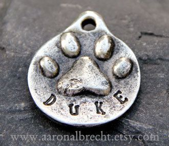 "$13.  1-1/4"" or 1-1/8"" diameter Pewter double-sided paw print pet ID tag personalized w/ pet's name stamped on front & 10-digit phone # on opposite side of tag (double sided).  By Aaron Albrecht.  LG size = 1-1/4""diameter.  Small sz = 1-1/8"" diameter.  Also come in other colors pewter & other pet ID tag designs @ aaronalbrecht Etsy shop"