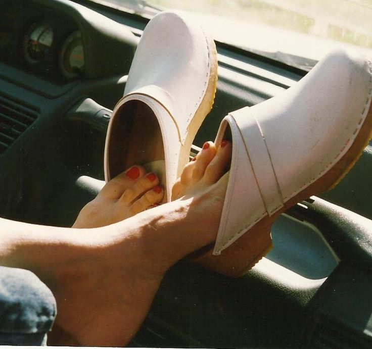 Gorgeous footplay with clogs on a dashboard.