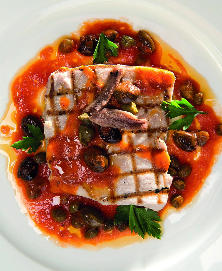 Dit heerlijke Italiaanse recept voor pesce spada alla puttanesca (zwaardvis met pittige saus) komt uit het prachtige boekPure Italiaanse keuken. De term 'puttanesca' wordt meestal gebruikt voor een Napolitaanse pastaschotel (volgens sommige versies afkomstig van het eiland Ischia). Deze vis kan dus geserveerd worden met penne of spaghetti. Maar ook met brood of crostini smaakt …