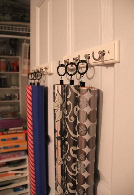 Wrapping Paper Storage Ideas - American Greetings Blog  PaperFlowers90 -  This is a fantastic and space saving idea for small rooms, i've had 2 rolls of wrapping paper for a while just hanging about my bedroom, so i  thought i would use this idea of using curtain hoops with curtain clips and hang them on some push-pins in the wall next to my bookshelves i turned into a shelving unit, it's off the floor and out of the way which is all i need.