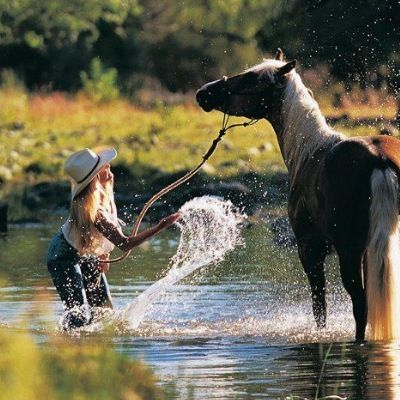 Cowgirl and horse playing in the water