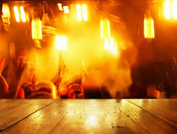 wood table background with blur orange light party in bar