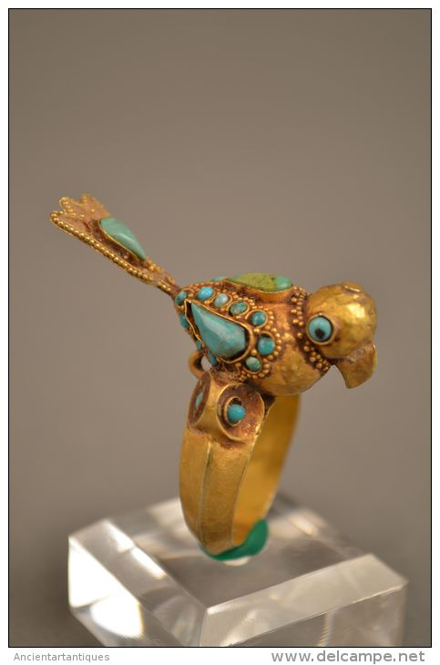 A Rare Islamic Gold Bird Ring circa 1200 A.DA   Gold Ring with Inlaid Termini in the Form of Seated Bird. Gold with turquoise onyx inlaid over the complete body of the bird.tail is bin broken but restored,otherwise intact  provenance: Dhr M.mazur jordanie 1977 . Dhr J. Nijenhuis Paris art market 2001 inner sise: 0.8 inch (2cm) weight:10.8 gram