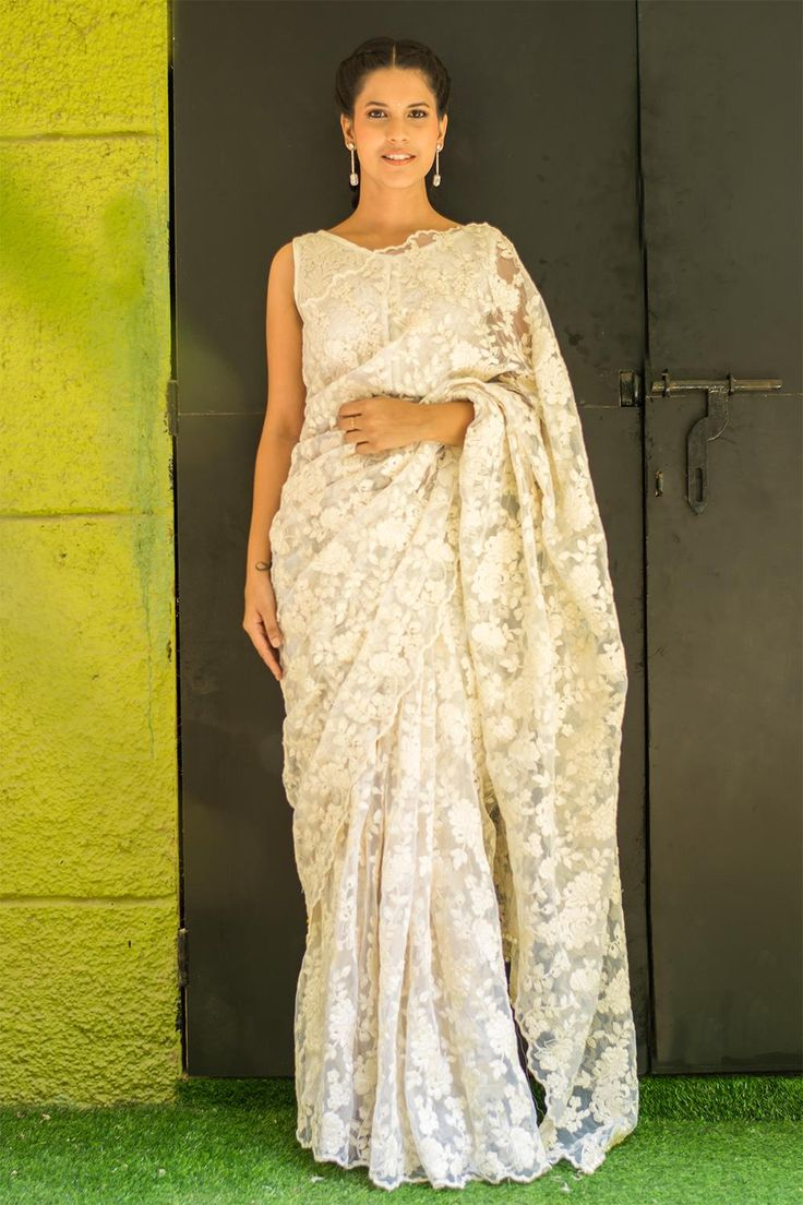 You would look like a fairy from fairyland in this gorgeous off white lacy net saree! With a threadwork border and pearl detailing for the pallu. Have all eyes upon you as gracefully descend down the stairs. White on white is a dreamy pairing any day. Or mix things up a bit by choosing a blouse in a pastel color.ACCOMPANIMENTS: All sarees are sold completely finished with falls (where required) and a free size underskirt. FABRIC: Saree – Off White net with lacy self threadworkDetail – Pearl…