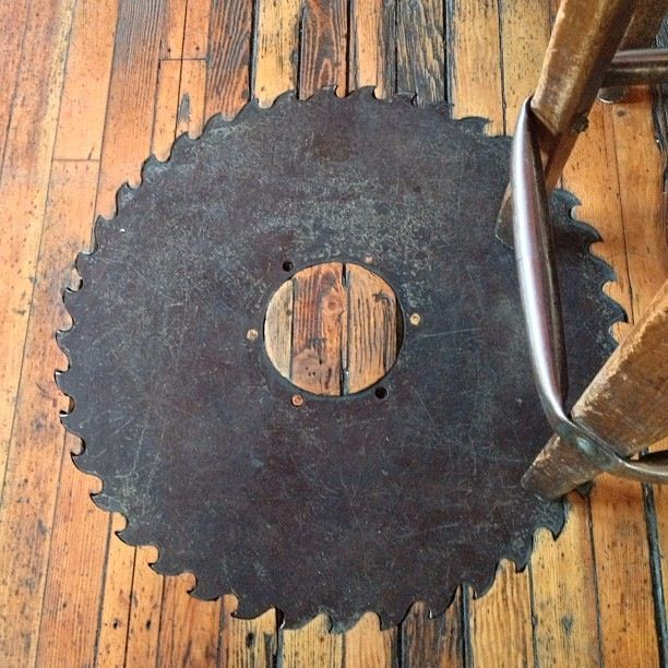 Saw blade inlay in wood floor --- this would be really great as a table top