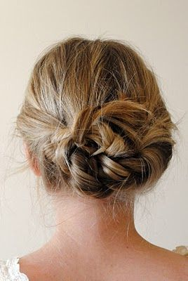 Part hair down center. Braid each pigtail back away from face. Tie braids in a knot. Bobby-pin loose ends.