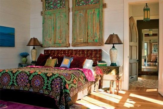 The master bedroom features Balinese windows and rich fabrics. Midway down the hall, a salvaged Gothic door opens to the powder room. Photo: Tony Giammarino