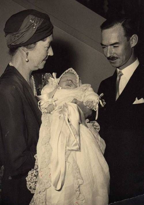 Grand Duke Jean of Luxembourg at the christening of his 1st son and 2nd child, Hereditary Prince Henri.  The baby is being held by Jean's mother, Grand Duchess Charlotte, whom Jean succeeded to the throne after her abdication in 1964.